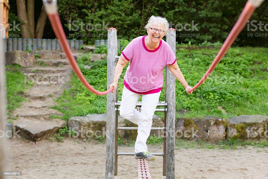 cheerful  senior woman on playground balancing stock photo
