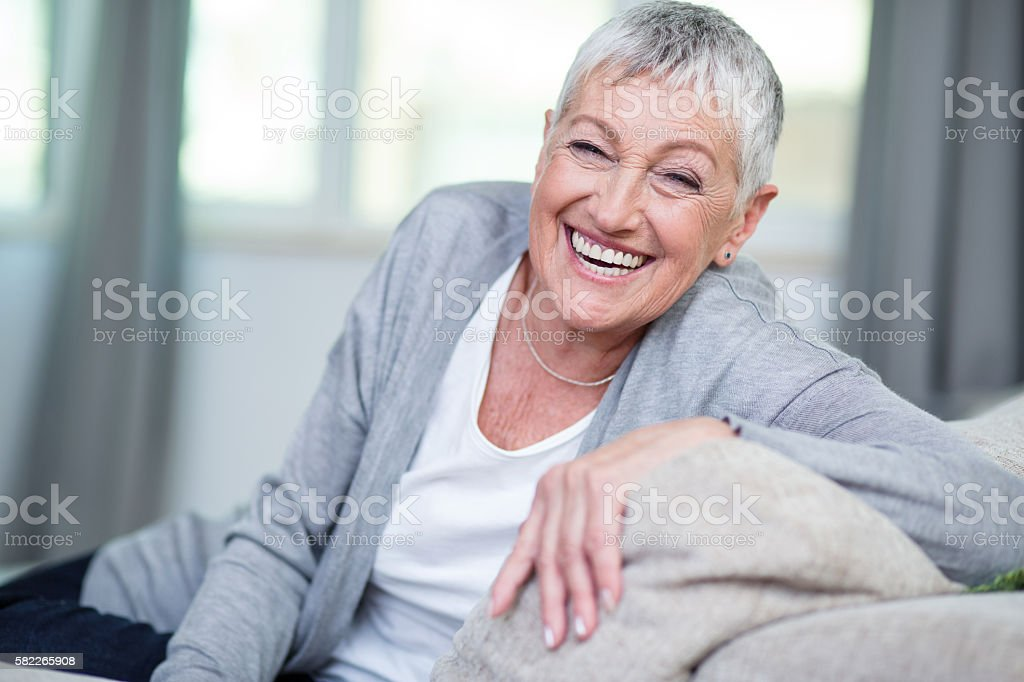 Cheerful senior woman sitting on a couch stock photo