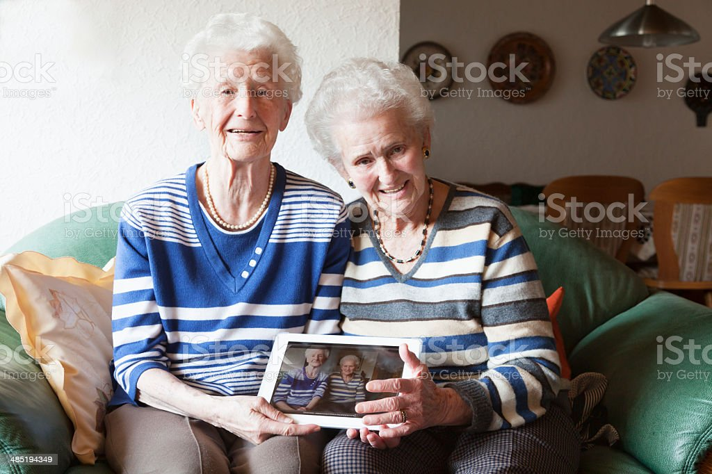 cheerful senior women with tablet pc showing their photo stock photo