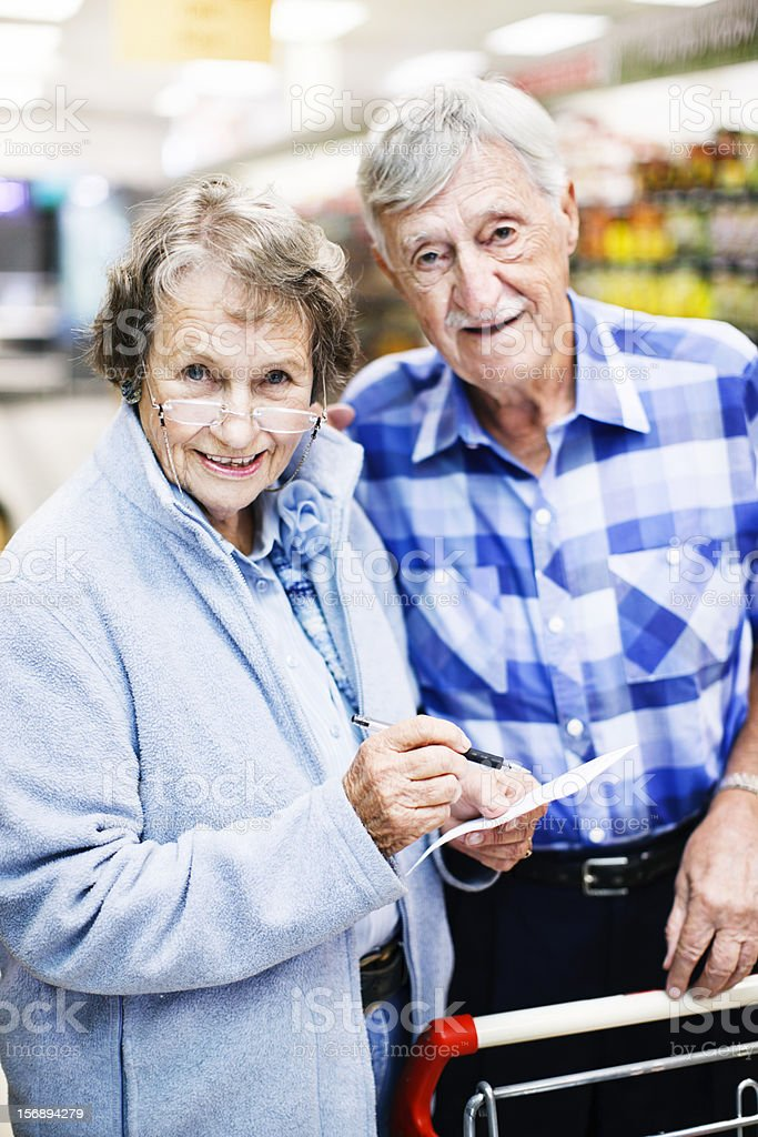Cheerful seniors check shopping list in supermarket stock photo