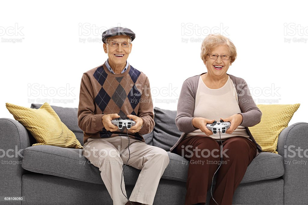 Cheerful seniors sitting on a sofa and playing video games stock photo