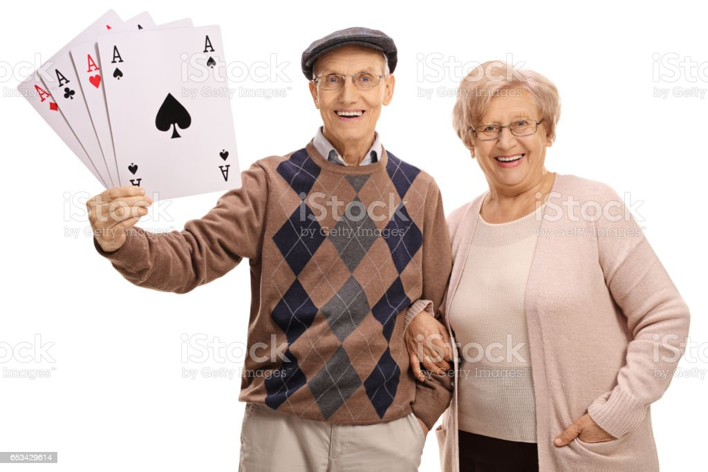 Cheerful seniors with four aces playing cards stock photo