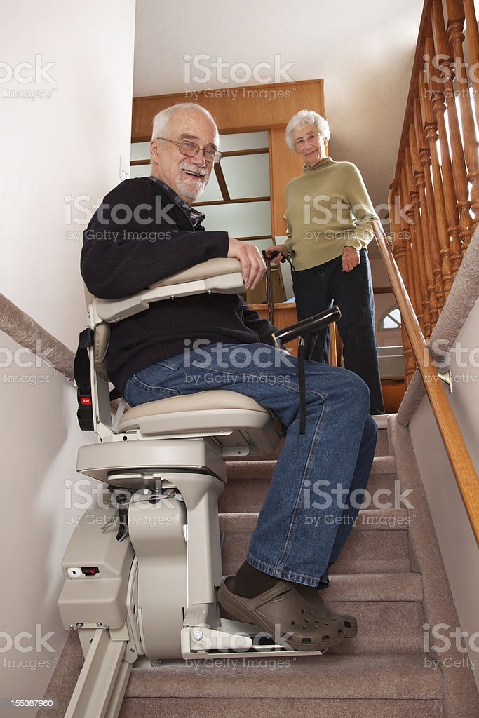Cheerful Seniors with Stairlift: Assisted Living stock photo