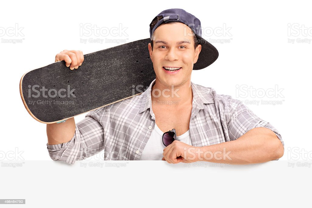 Cheerful skater posing behind a billboard stock photo