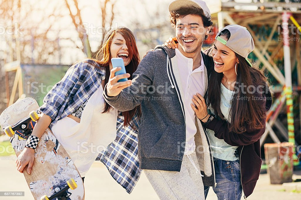 Cheerful skaters with phone on the playground stock photo