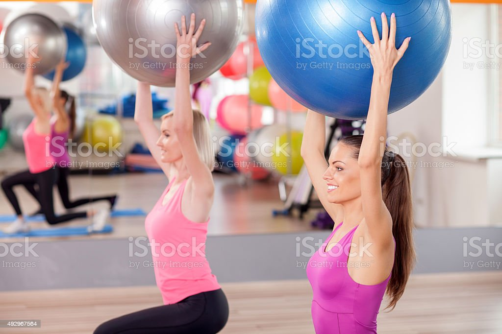 Cheerful slim girls are doing exercise in gym stock photo