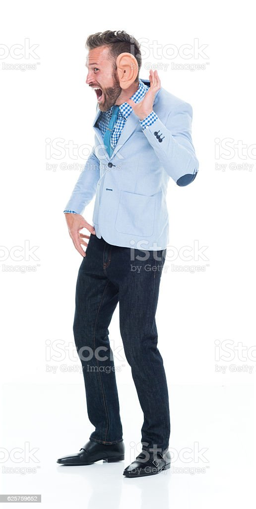 Cheerful smart casual man listening stock photo