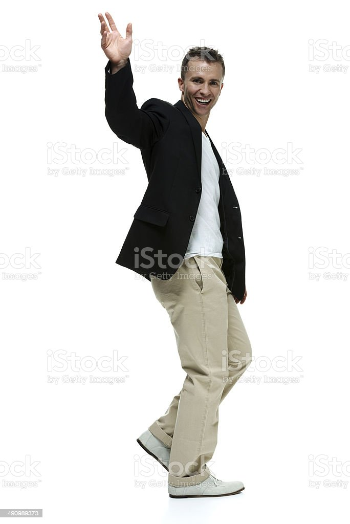 Cheerful smart casual man walking & waving hand royalty-free stock photo