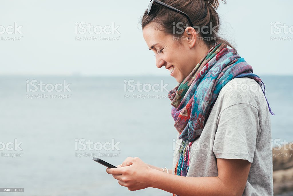 cheerful smiley woman by the sea texting on phone stock photo