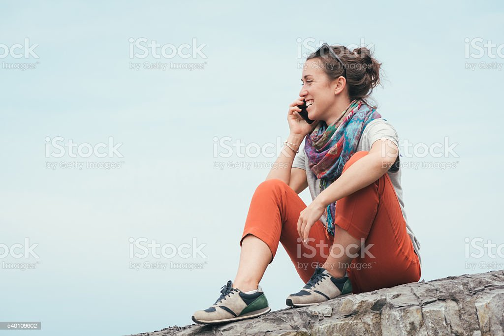 cheerful smiley woman sitting by the sea talking on phone stock photo