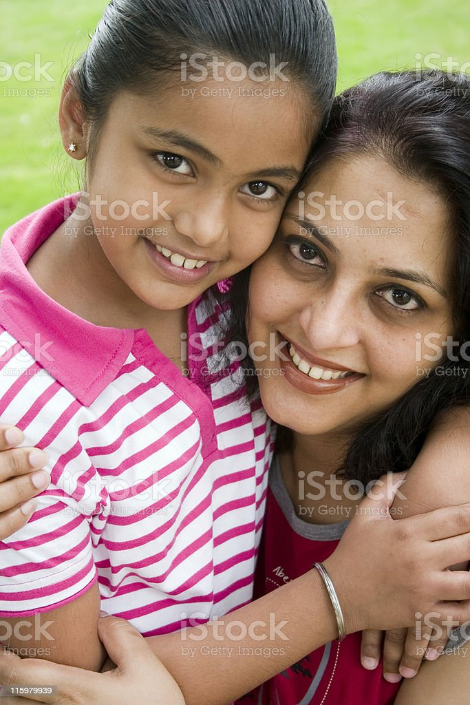 Cheerful Smiling Loving Indian Mother Daughter Hug Embracing Vertical Grass stock photo