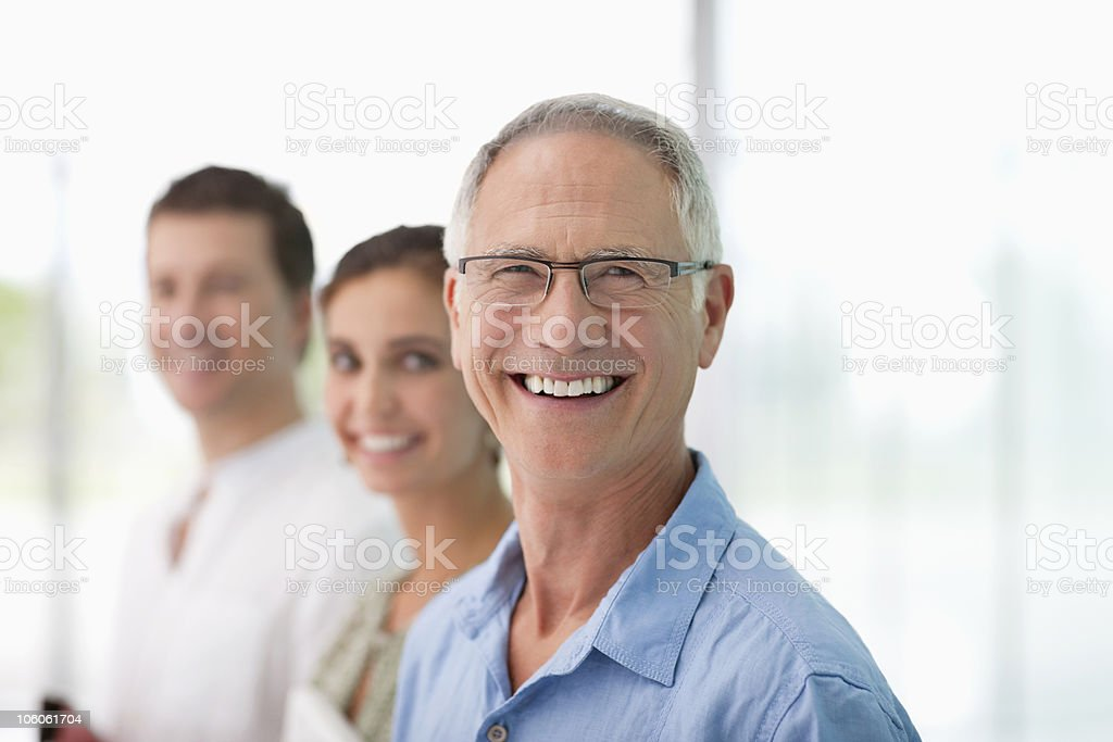 Cheerful smiling senior man with his colleagues royalty-free stock photo