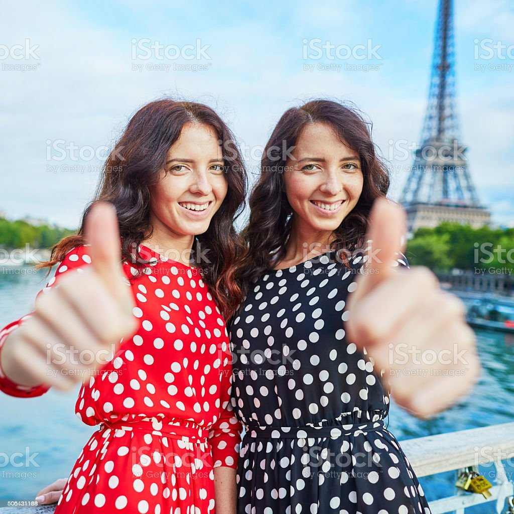 Cheerful smiling twin sisters in front of Eiffel Tower stock photo