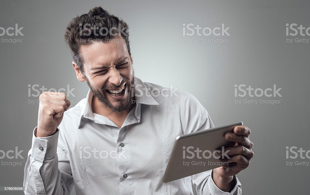 Cheerful smiling young man with tablet stock photo