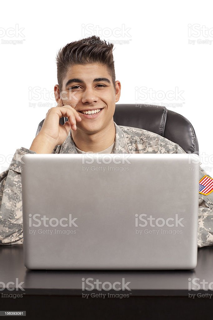 Cheerful soldier sits at his desk royalty-free stock photo