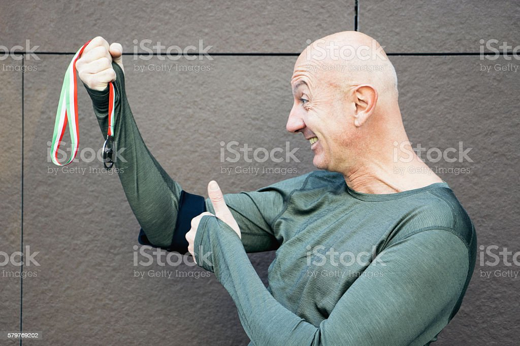 Cheerful Sportsman Holding A Victory Medal stock photo