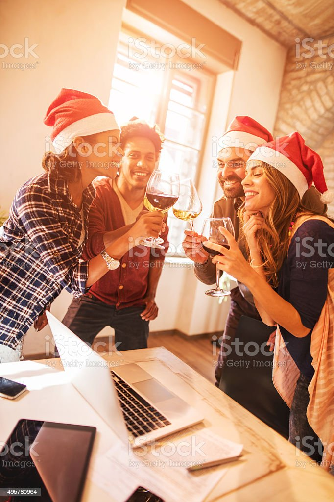 Cheerful start up team toasting to upcoming New Year. stock photo