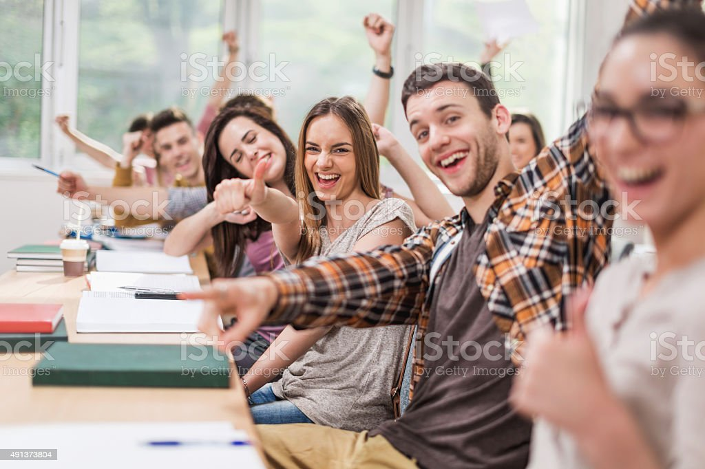 Cheerful students celebrating in classroom and looking at camera stock photo