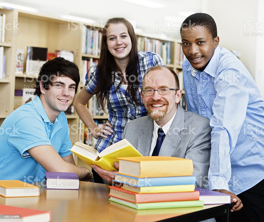 Cheerful study group: three students and teacher in library royalty-free stock photo