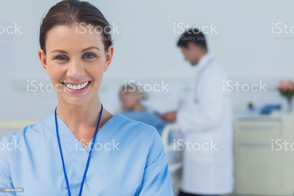 Cheerful surgeon posing with doctor attending patient on backgro stock photo