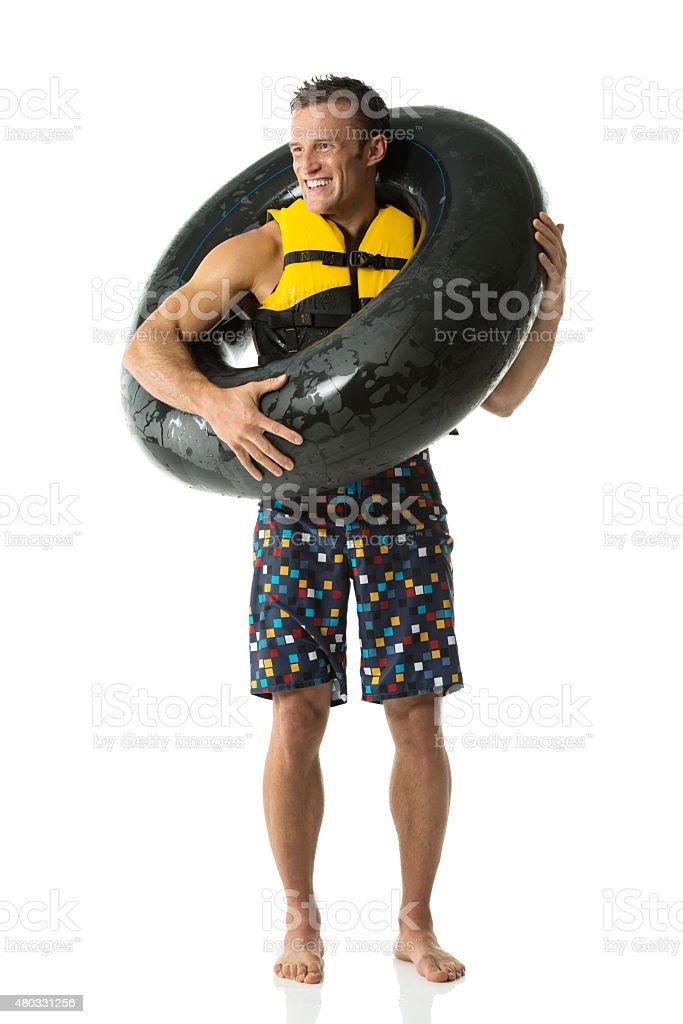 Cheerful swimmer holding inner tube stock photo