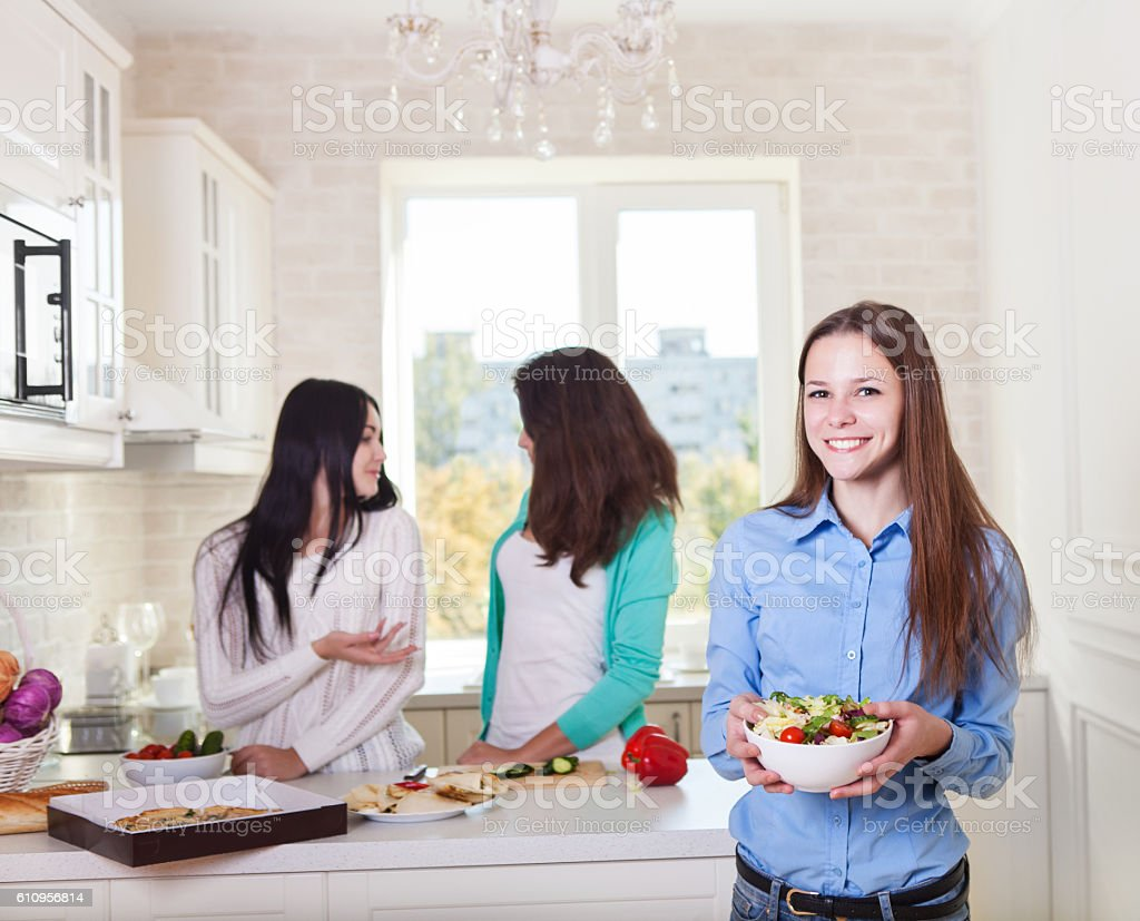 Cheerful teen girls preparing salad together stock photo