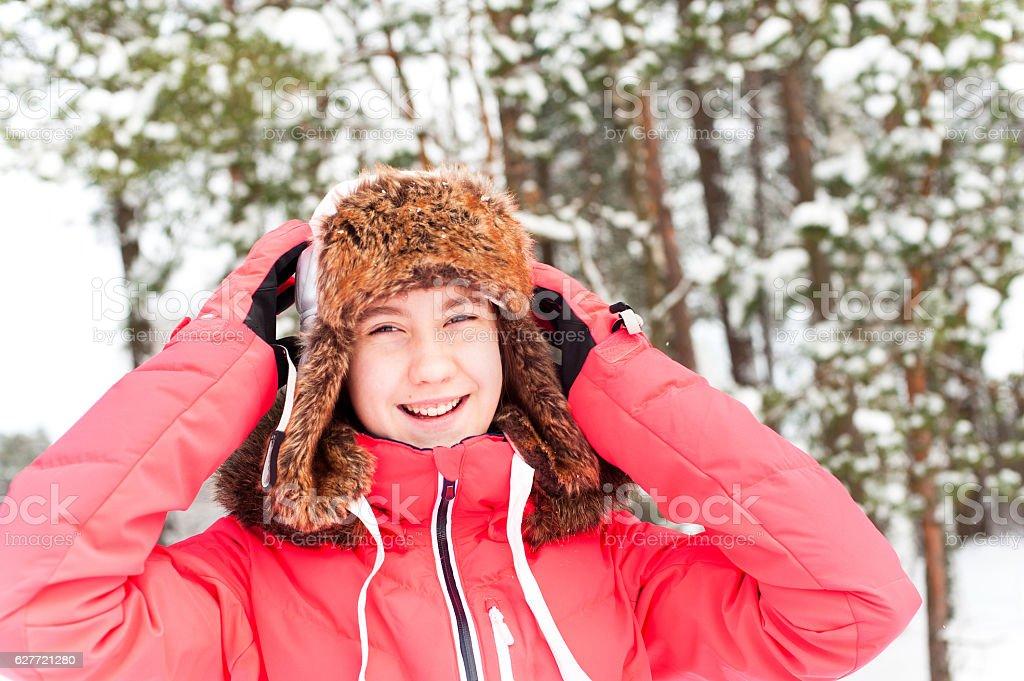 Cheerful teenage girl in warm earflap having fun in winter forest. stock photo