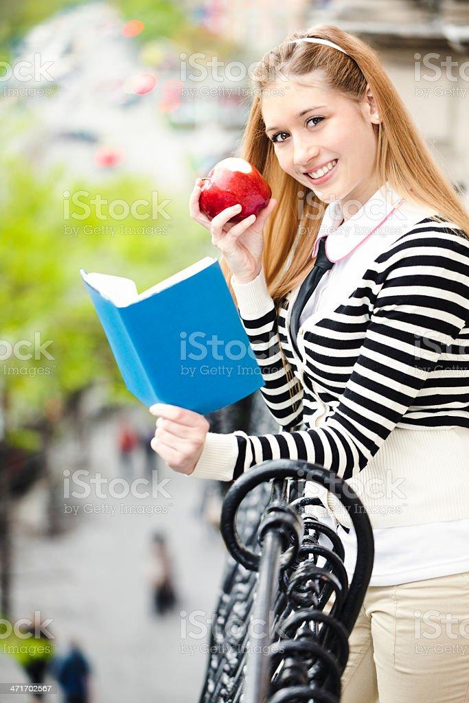 Cheerful teenage girl reading royalty-free stock photo
