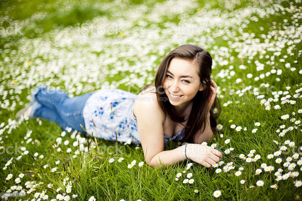Cheerful teenage girl sitting in grass royalty-free stock photo