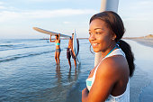 Cheerful teenage girl wades in shallow water with surfboard