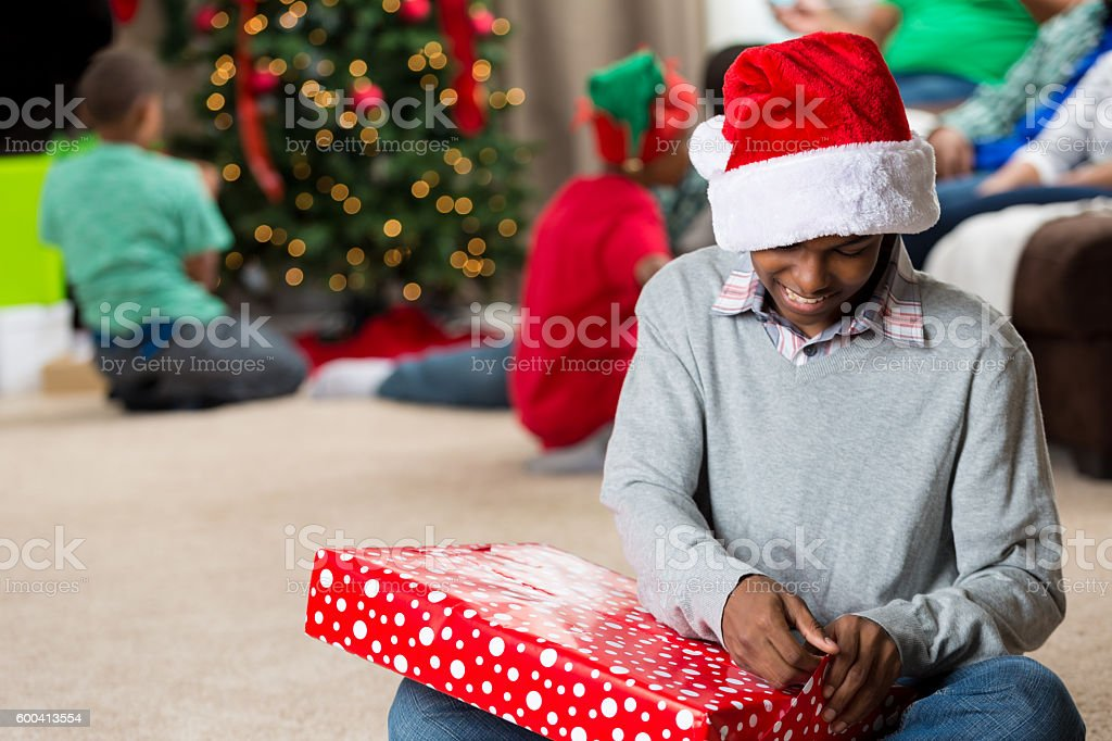 Cheerful teenager wears a Santa hat and opens Christmas presents stock photo