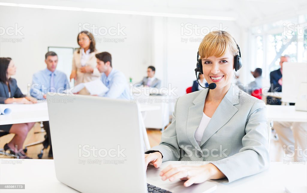 Cheerful Telecommunications Agent on a Busy Office stock photo