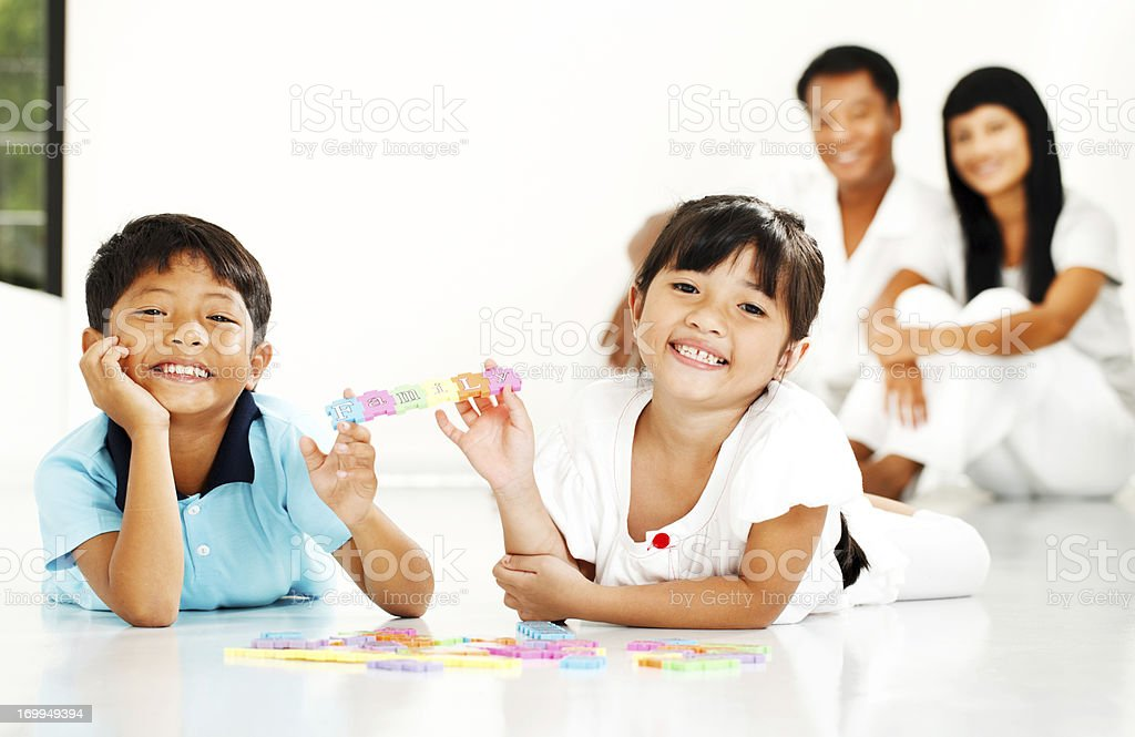 Cheerful Thai children playing with puzzle at home royalty-free stock photo