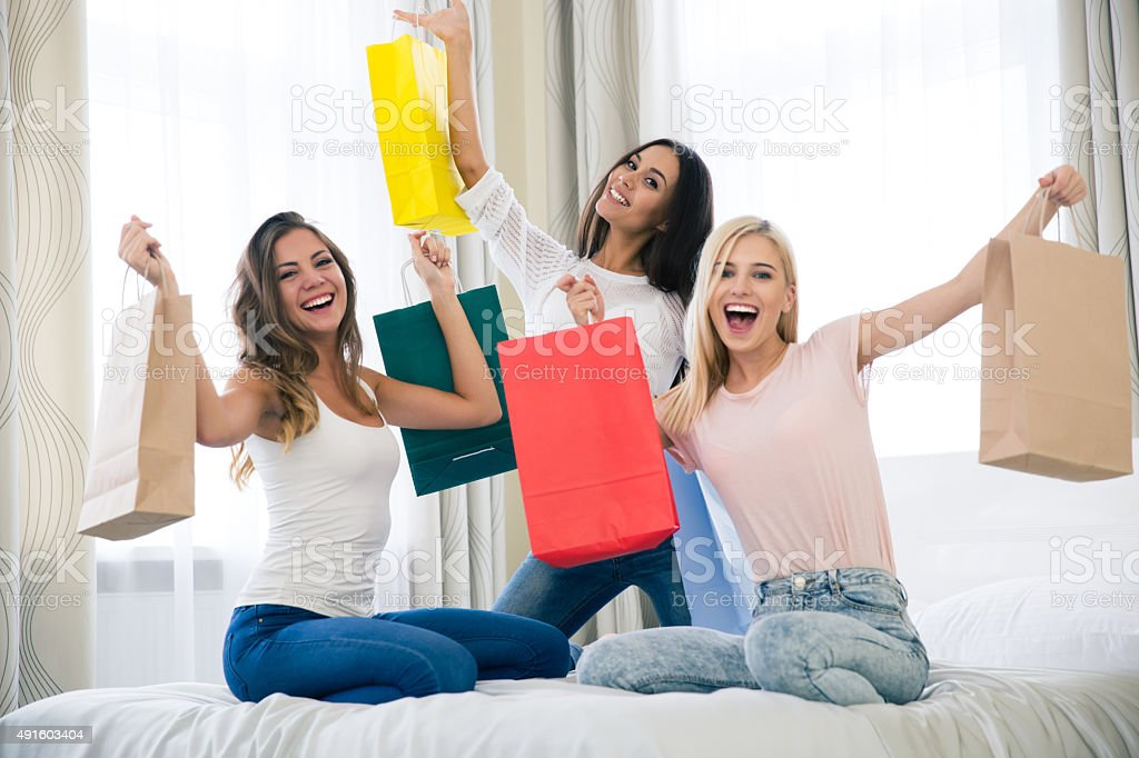 Cheerful three girlfriends with many shopping bags stock photo