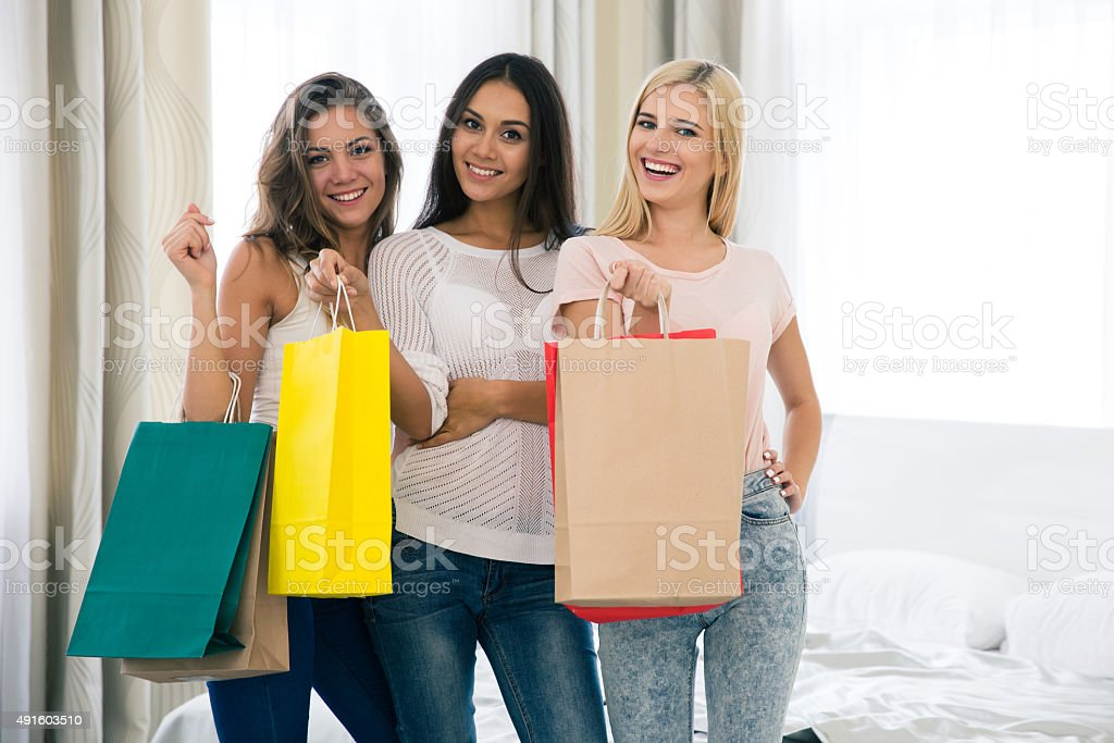 Cheerful three girls with many shopping bags stock photo