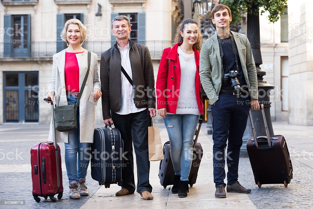 Cheerful tourists with luggage pose outdoors stock photo
