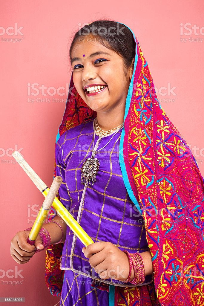 Cheerful Traditional Indian Attractive Beautiful Teenager Girl Holding Dandiya Sticks stock photo