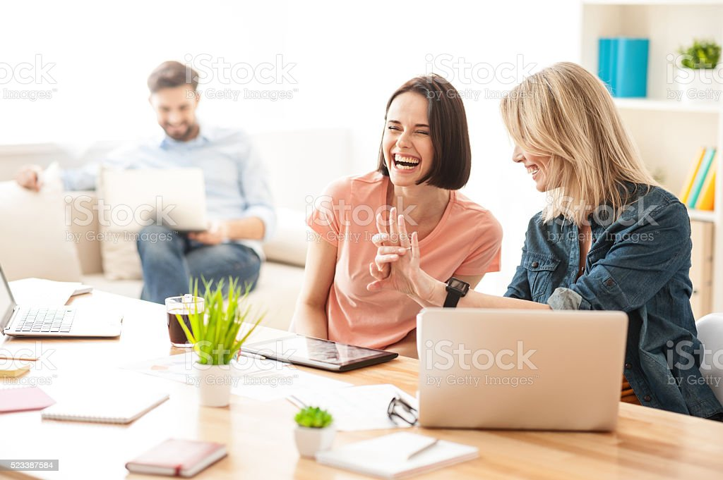 Cheerful two female workers are talking with joy stock photo
