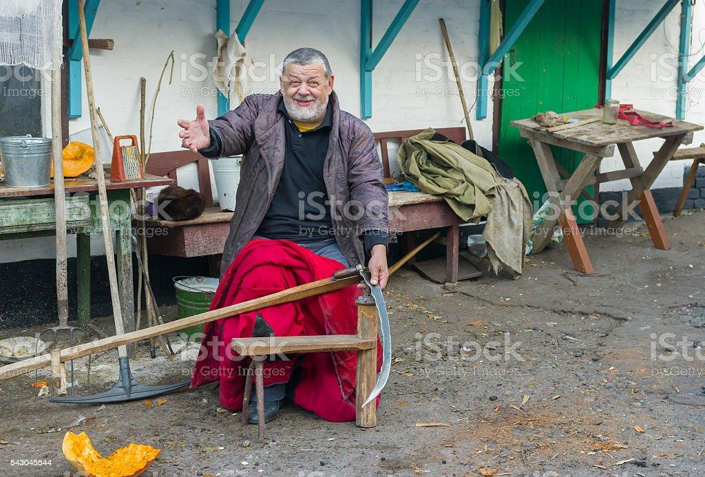 Cheerful Ukrainian peasant getting ready to whet a scythe stock photo