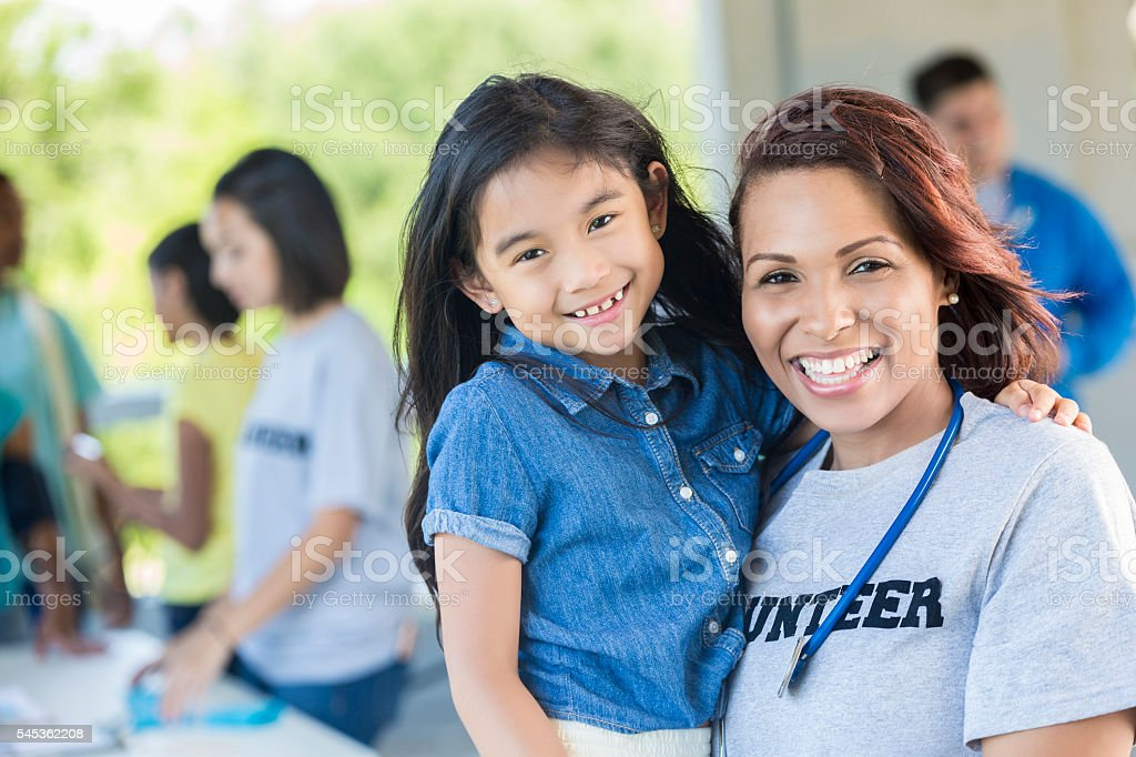 Cheerful volunteer holding an adorable young girl stock photo