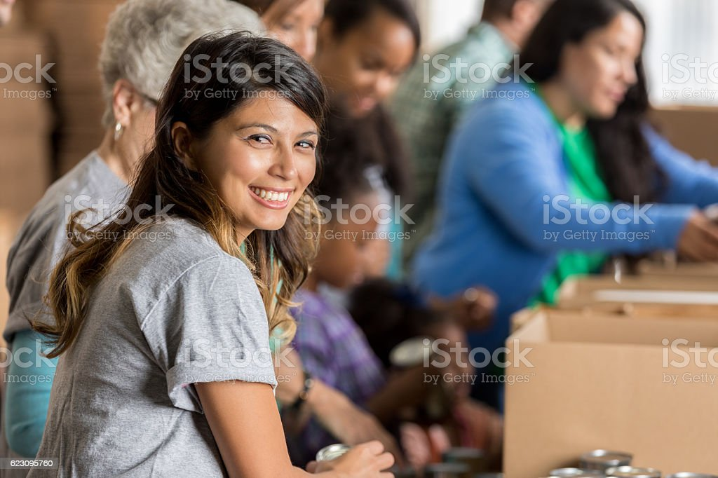 Beautiful mid adult Hispanic woman smiles while helping pack boxes at...