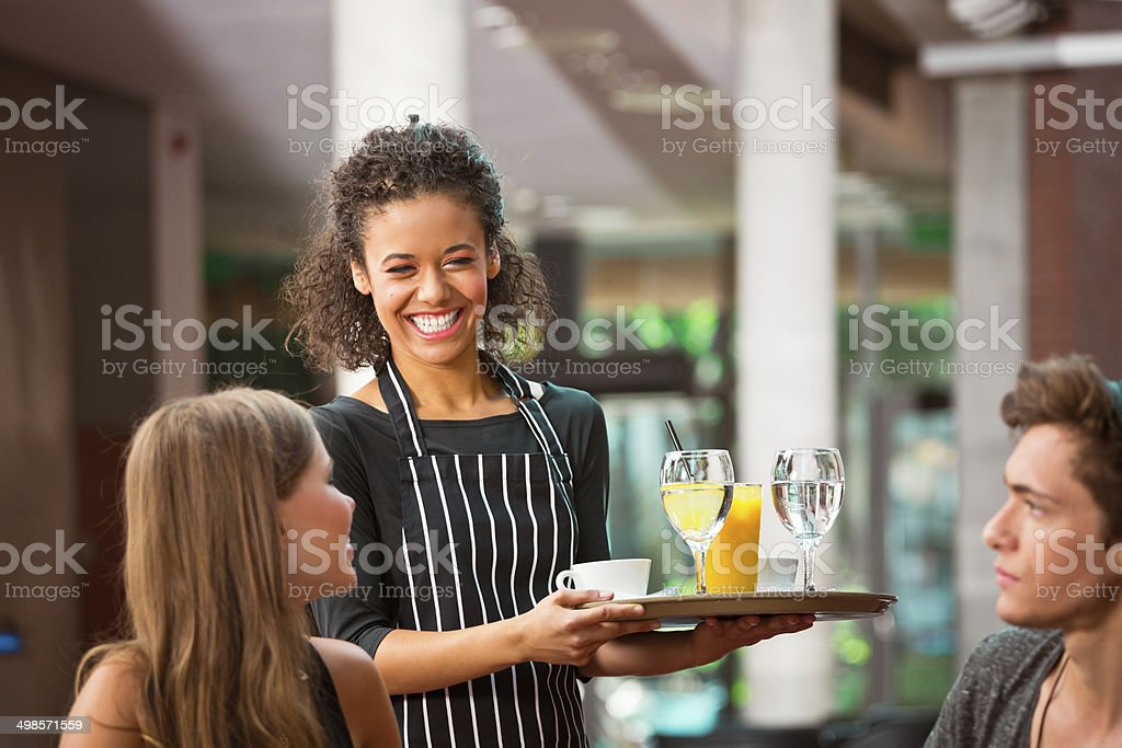 Cheerful waiter serving drinks stock photo