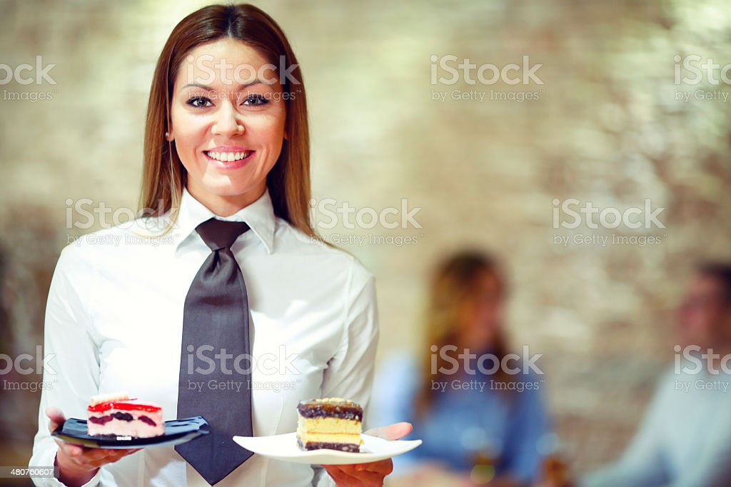 Cheerful waitress with desserts. stock photo