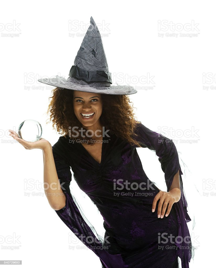 Cheerful witch holding crystal ball stock photo