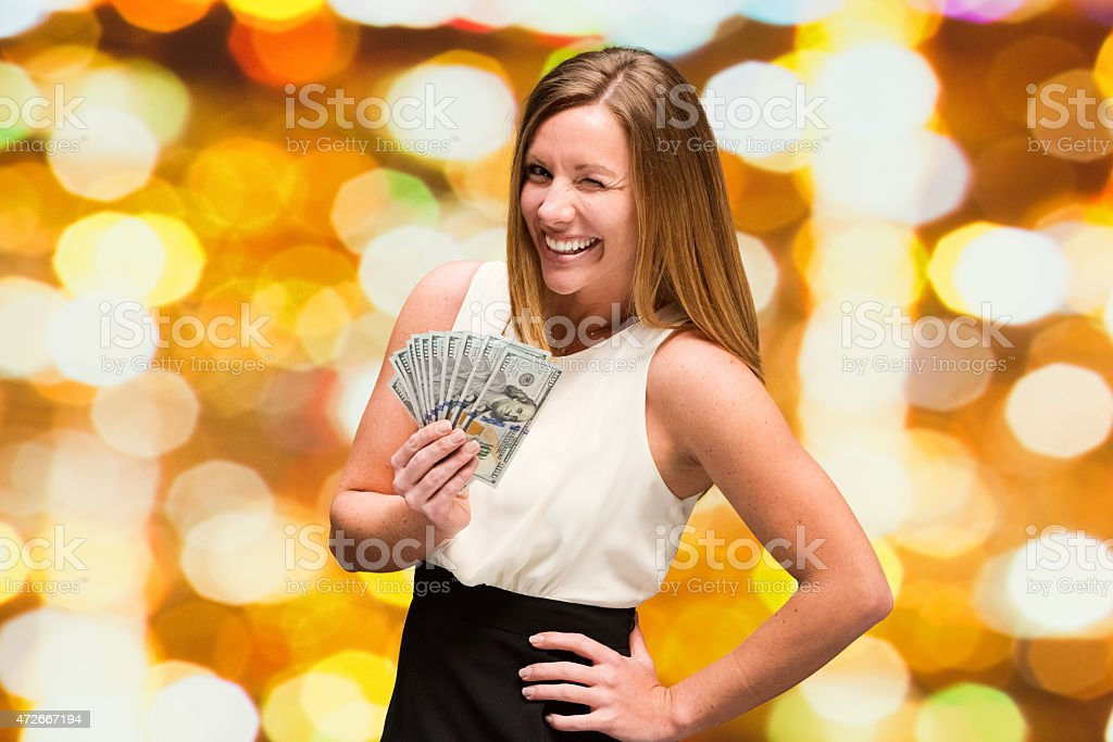 Cheerful woman being happy with money and winking stock photo