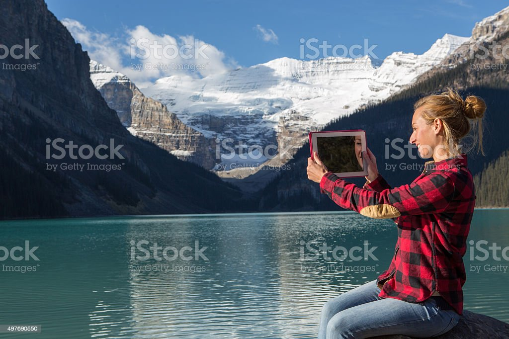 Cheerful woman by the mountain lake using digital tablet stock photo