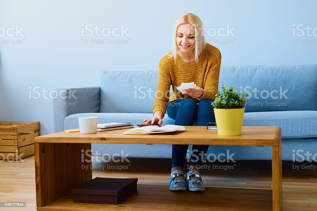Cheerful woman counting home finance on calculator stock photo