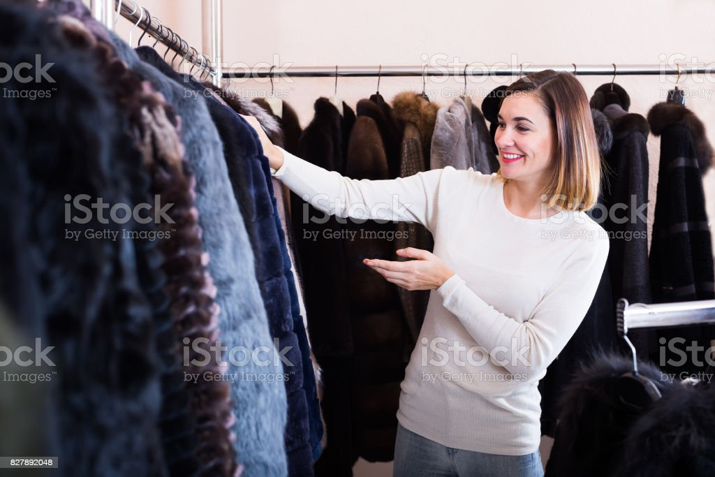 Cheerful woman customer examining best fur coats stock photo