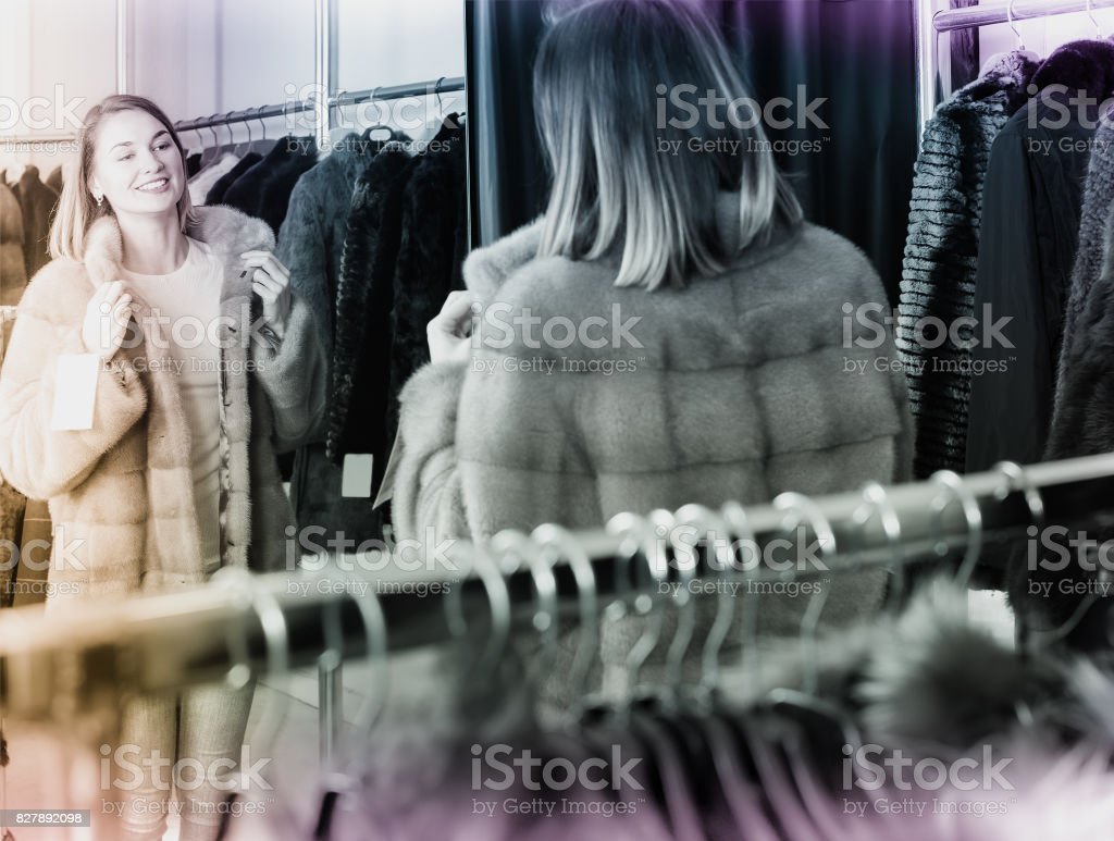 Cheerful woman customer examining new fur coat stock photo