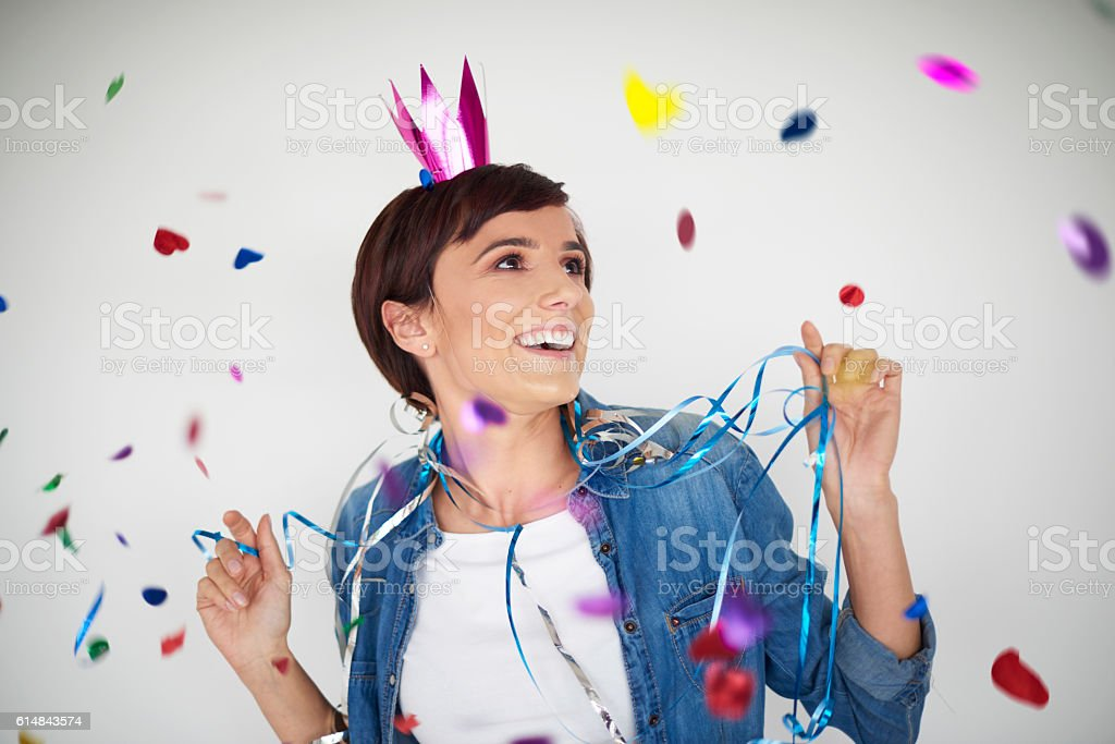 Cheerful woman dancing among colorful confetti pieces stock photo
